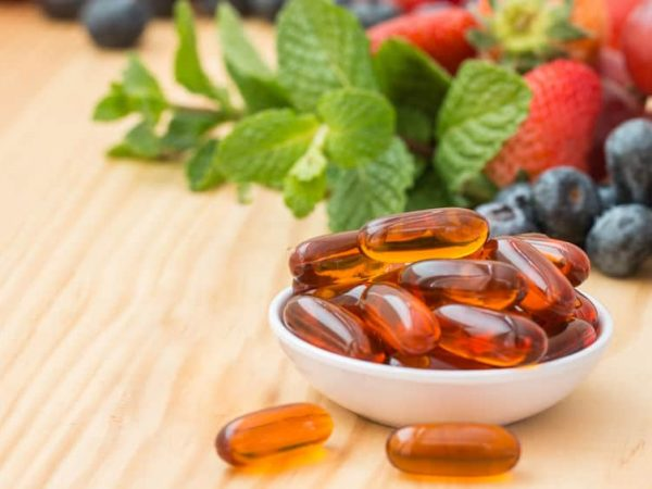 Lecithin gel vitamin supplement capsules on wooden table.