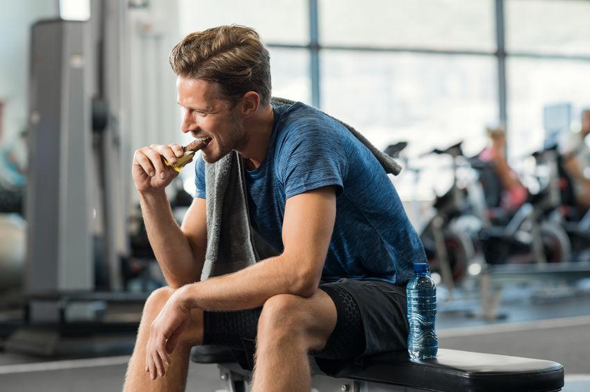 Hombre comiendo barra de proteínas en gimnasio