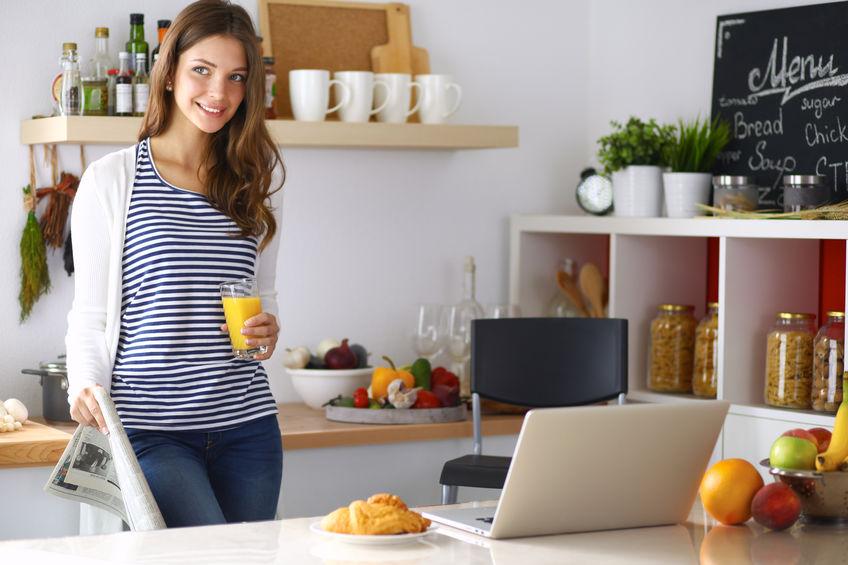 Mujer en la cocina con un vaso de jugo de naranja en la mano en la computadora portátil en la mesa