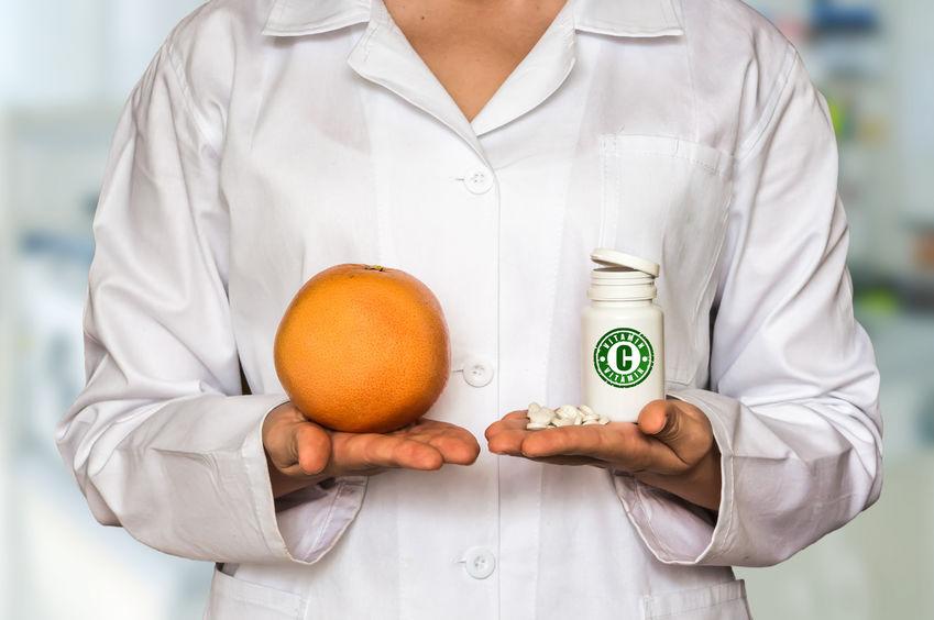 femme médecin tenant une orange dans la main droite et une bouteille de vitamine C dans la main gauche