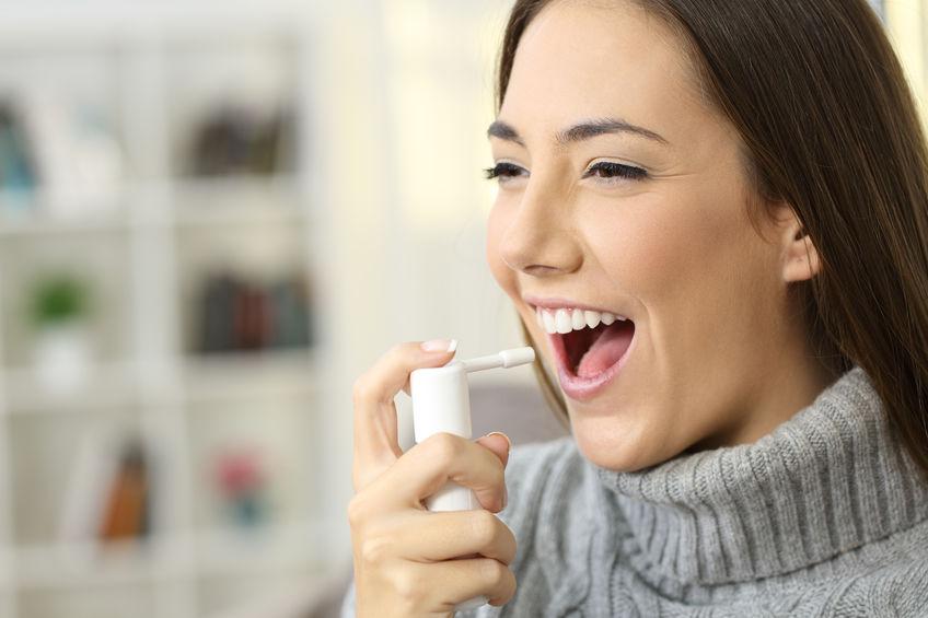 Mujer feliz vistiendo jersey usando un aerosol analgésico para suavizar la garganta sentado en un sofá en el interior de una casa