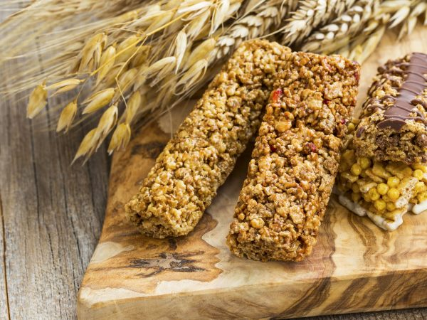 Healthy granola cereal bars with wheat ears on wooden board