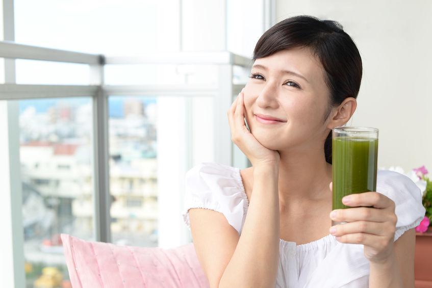 Mujer con una bebida en la mano pensando