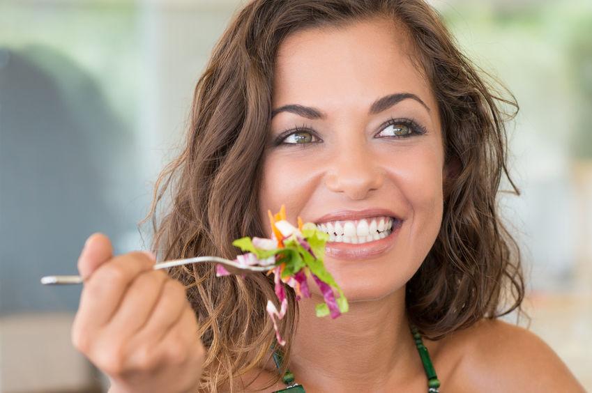 Mujer sonriendo mientras come una enslada