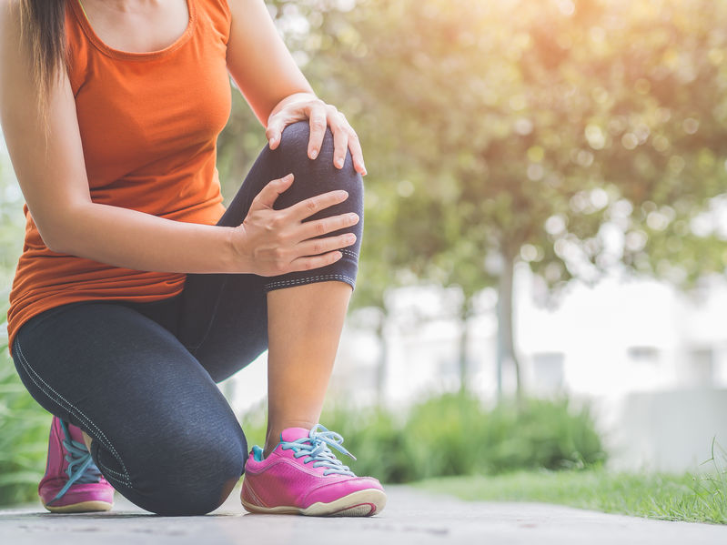 Mujer con ropa de ejercicios tocándose la rodilla