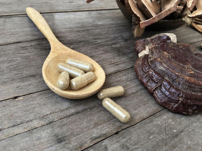 Imagen de capsulas sobre una cuchara sobre superficie de madera