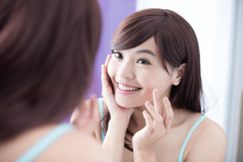 Mujer asiatica sonriendo frente al espejo