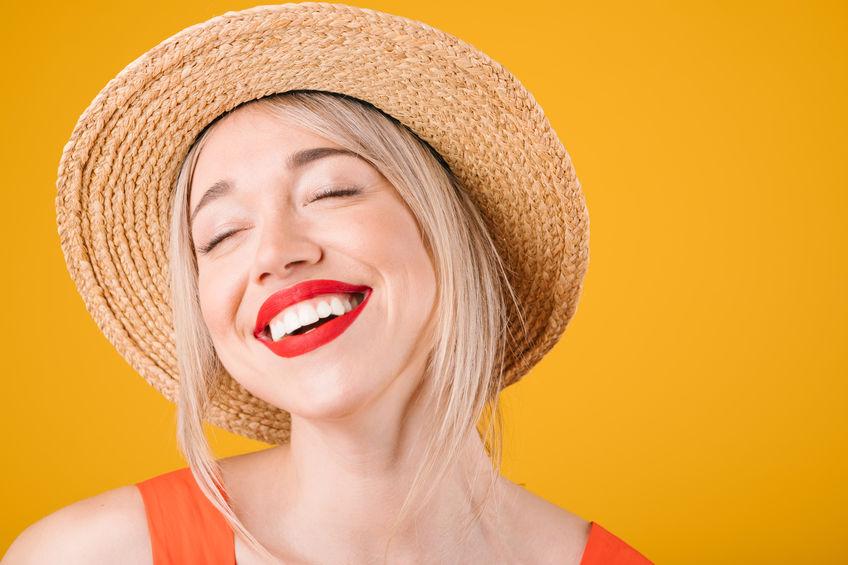 ujer rubia sonriendo con fondo naranja